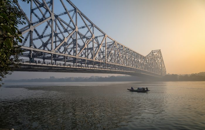 Historic Howrah bridge on river Hooghly on a misty winter morning with a fishing boat passing the bridge via Depositphotos